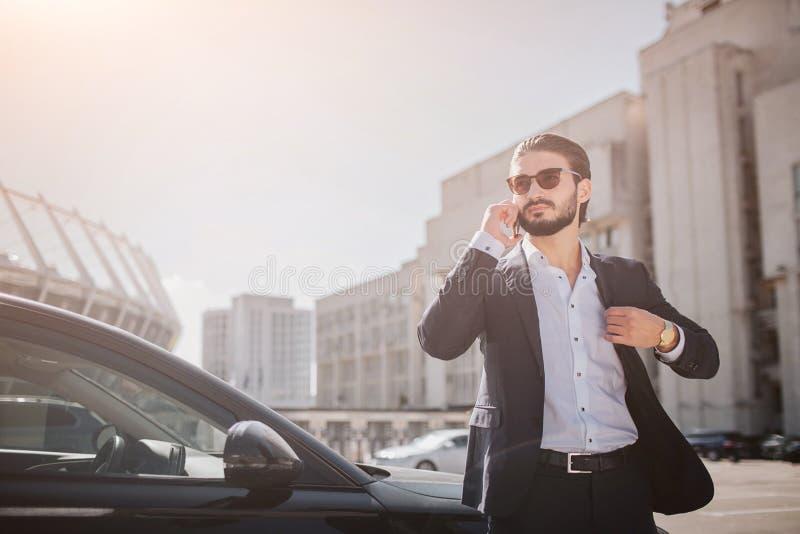 Suporte sério e bem vestido do homem novo no carro na série e negociações no telefone Guarda a peça do revestimento traseiro O in fotografia de stock
