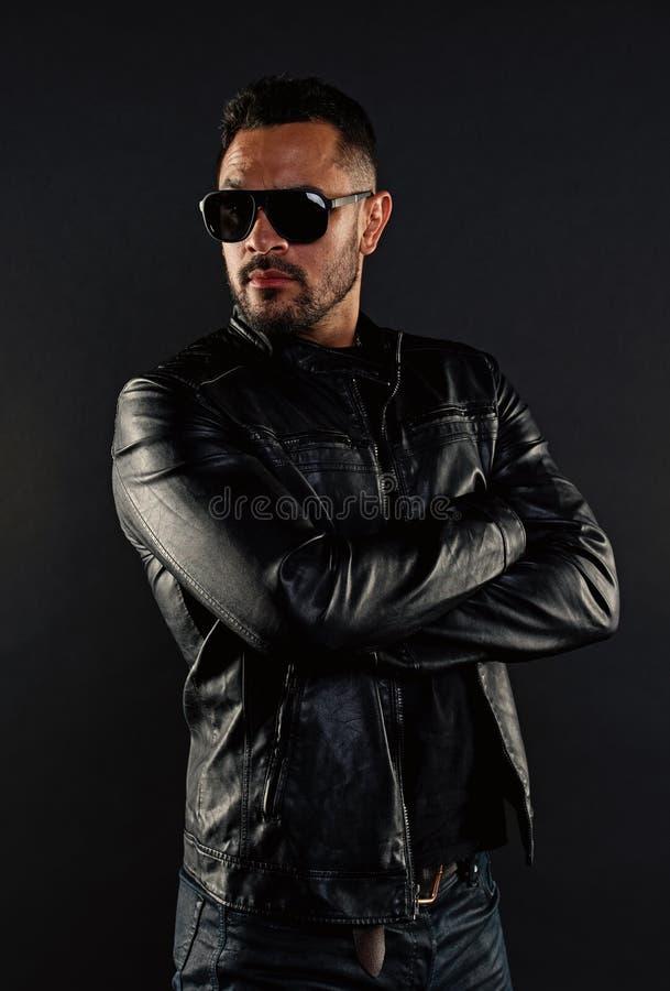 Suporte seguro do homem com os bra?os dobrados Homem farpado em ?culos de sol na moda Modelo de forma no casaco de cabedal e nas  imagens de stock