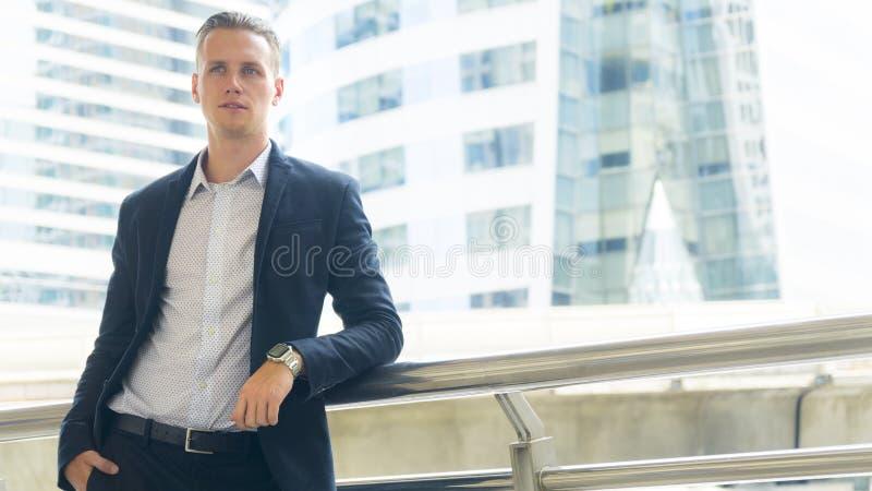 suporte seguro do homem do negócio esperto no espaço público exterior imagens de stock royalty free