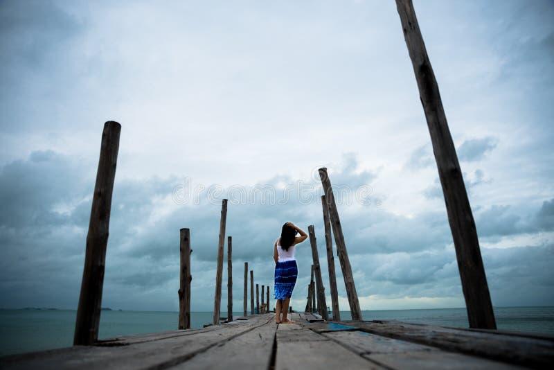 Suporte triste e só da mulher apenas no a ponte de madeira imagem de stock royalty free