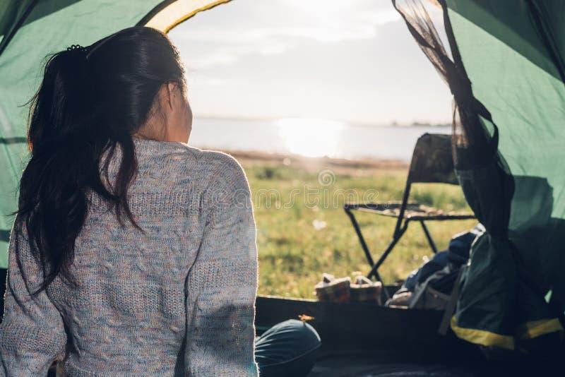 Suporte uma mulher dentro da barraca de acampamento da vista no verão fotografia de stock