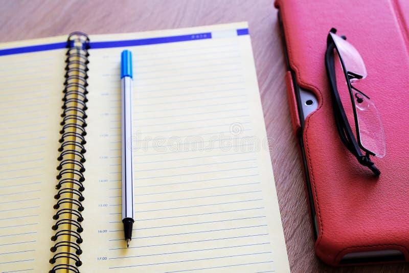 Suporte vermelho da caixa do tablet pc para a tabuleta um grande acessório Um caderno detalhado e vidros Para o trabalho fotos de stock