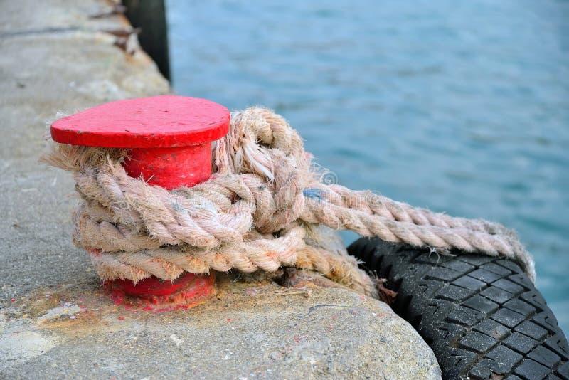Suporte vermelho no cais com uma corda e um pneumático foto de stock