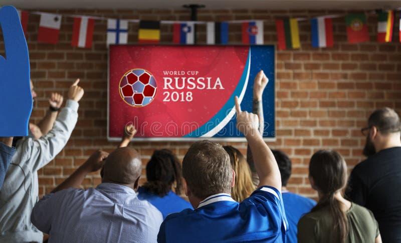 Suportes alegres que olham o futebol no bar foto de stock