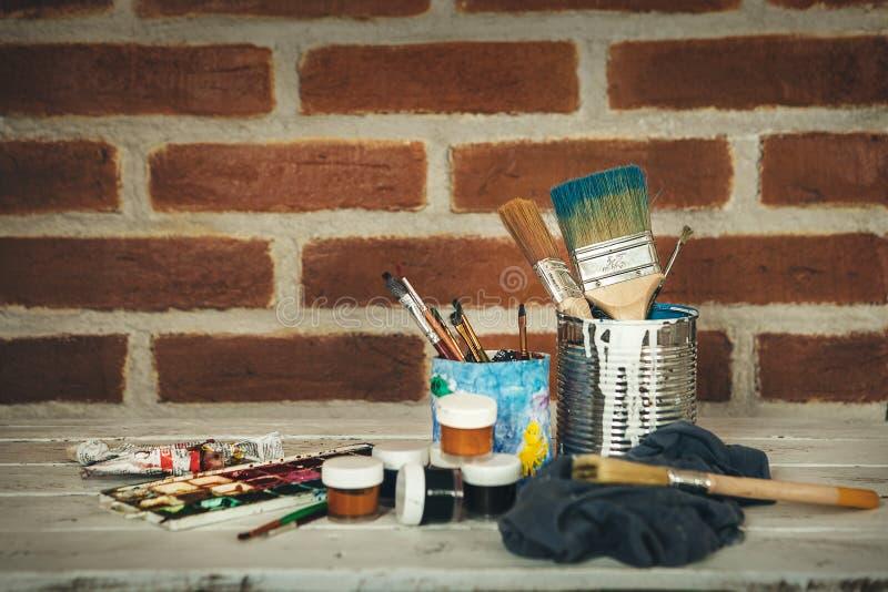 Suportes da pintura no fundo da parede de tijolo foto de stock