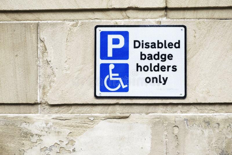 Suportes de crachá deficientes somente no sinal do parque de estacionamento na parede imagens de stock