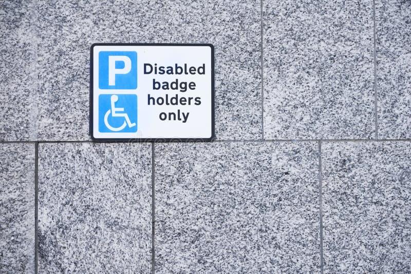 Suportes de crachá deficientes somente no sinal do parque de estacionamento na parede foto de stock royalty free