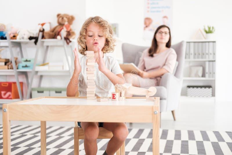 Suportes de madeira do desenvolvimento nas mãos de uma criança durante uma reunião educacional da terapia com um pedagogo em um o fotografia de stock royalty free