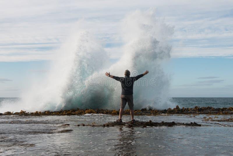 Suportes do homem na frente de espirrar a onda imagens de stock royalty free