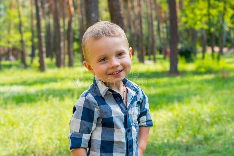 Suportes do rapaz pequeno e sorriso no parque em um dia ensolarado imagens de stock royalty free
