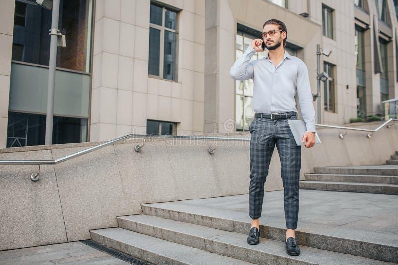 Suportes e poses à moda sérios e conentrated do homem de negócios Guarda o portátil à disposição e o telefone perto da orelha Olh imagens de stock