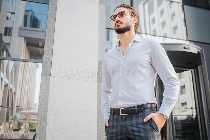 Suportes e poses modelo masculinos bonitos Olha à moda O homem novo veste óculos de sol e olha para a frente É atrativo imagem de stock