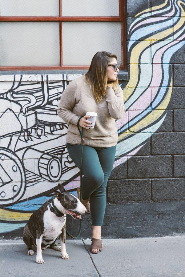 Suportes milenares de Latina contra a parede com seu cão de estimação bull terrier que senta-se por seu lado fotografia de stock