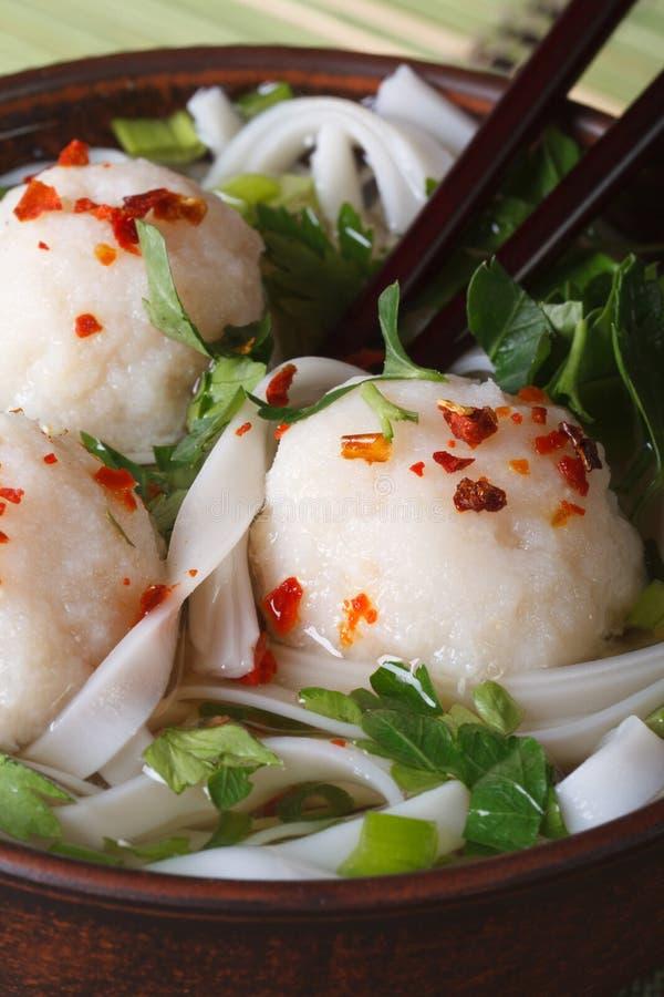 Suppe mit den Fischbällen, Nudeln und frischen Kräutern Makro vertikal lizenzfreie stockfotos