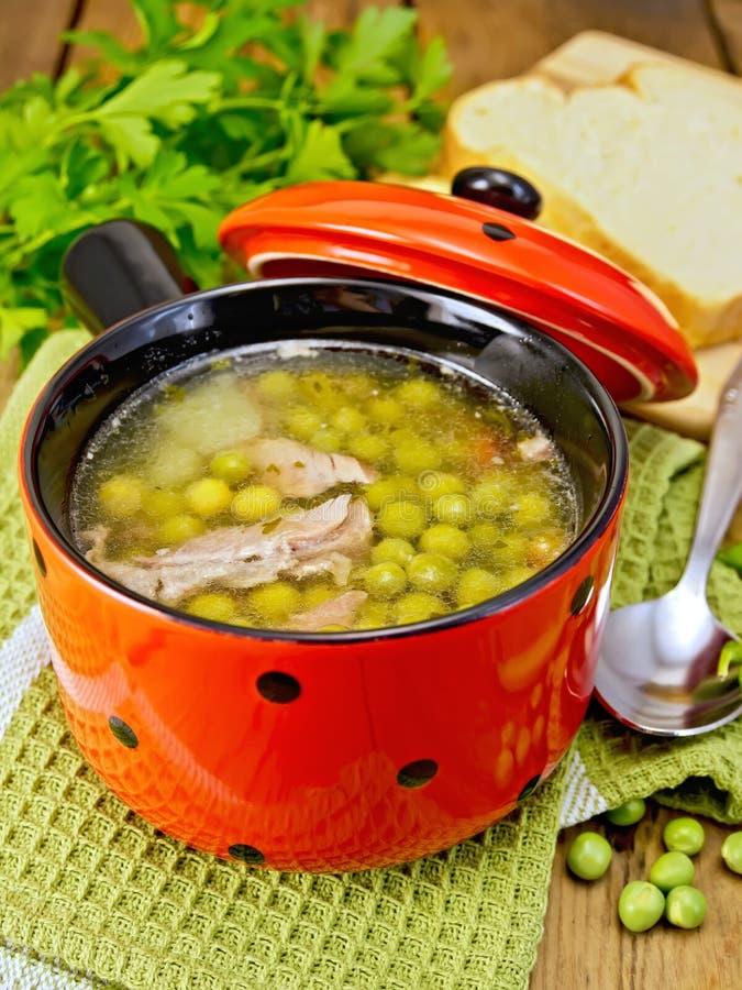 Suppe von den grünen Erbsen mit Fleisch in der roten Schüssel und im Brot an Bord lizenzfreie stockfotografie