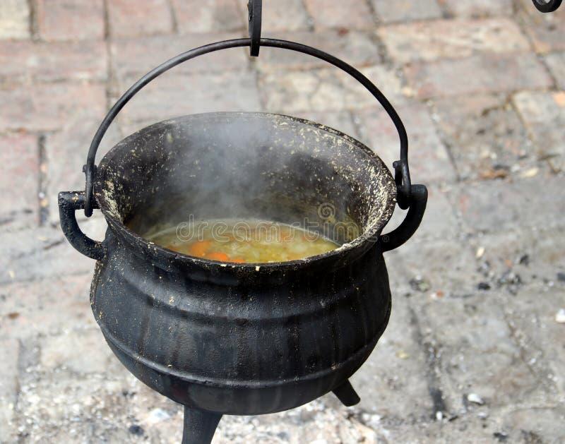 Suppenkochen in einem Topf aus Gusseisen lizenzfreie stockfotos