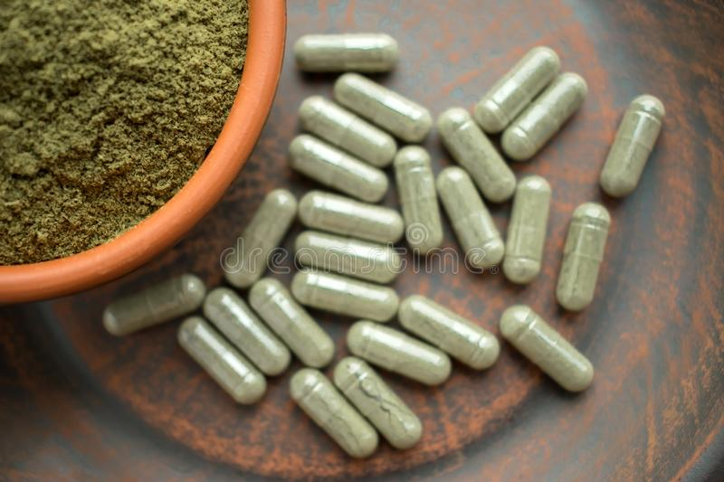 Supplement kratom groen capsules en poeder op bruine plaat kruid stock afbeelding