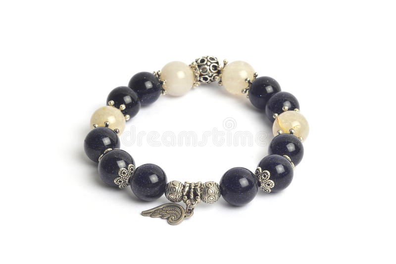 Supplement a richness and good fortune by blue sand stone Silver sand stone and golden rutillated quartz bracelet amulet stock photography