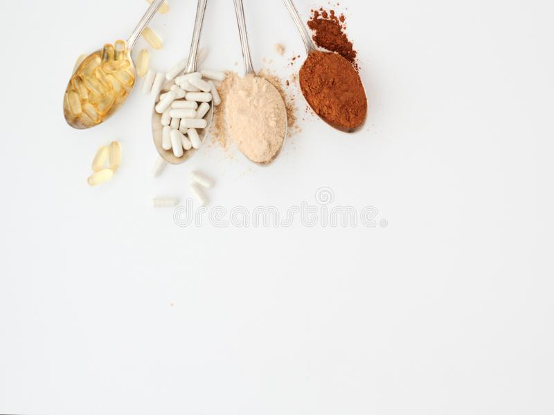 Supplements for PCOS Polycystic Ovary Syndrome. Exemplary supplements for PCOS Polycystic Ovary Syndrome displayed on spoons. Omega 3, probiotics, maca powder stock photography