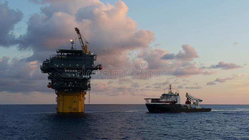 Another day in the oilfield. A supply boat next to a Floating Production and Storage spar in Gulf of mexico stock photography