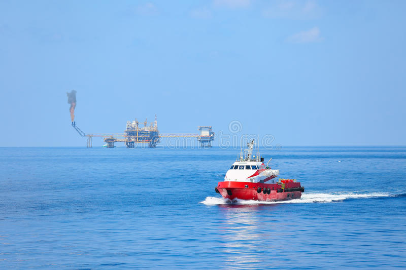 Supply boat transfer cargo to oil and gas industry and moving cargo from the boat to the platform, boat waiting transfer cargo. And crews between oil and gas stock photo