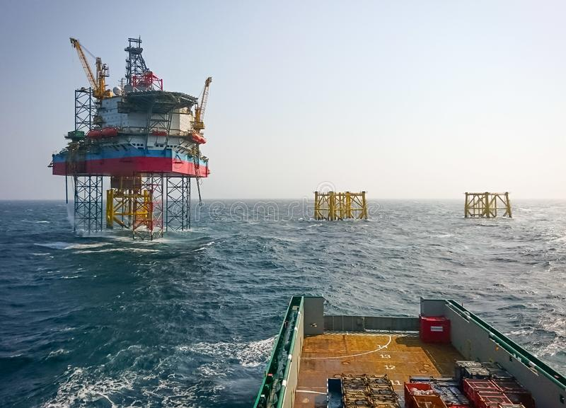 Supply vessel approaching offshore platform. Supply vessel backing into offshore jack up drilling rig in the North Sea royalty free stock image