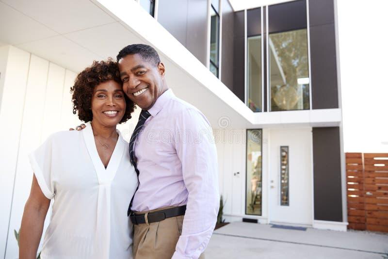 Support âgé moyen de couples d'Afro-américain en dehors du regard à la caméra devant leur maison moderne, fin  photographie stock libre de droits