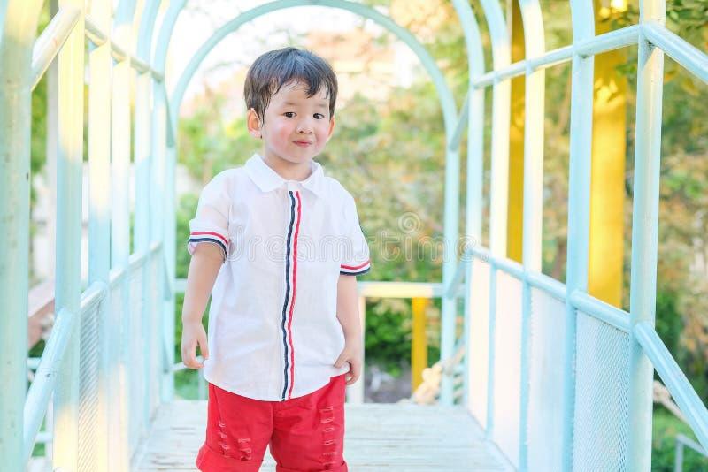 Support asiatique d'enfant de plan rapproché sur le pont en acier au fond de terrain de jeu avec la lumière du soleil photographie stock libre de droits