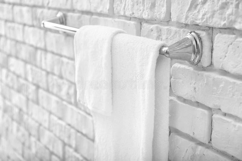 Support avec des serviettes sur le mur de briques photos libres de droits