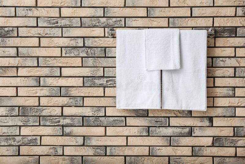 Support avec les serviettes éponge blanches sur le mur de briques photographie stock libre de droits