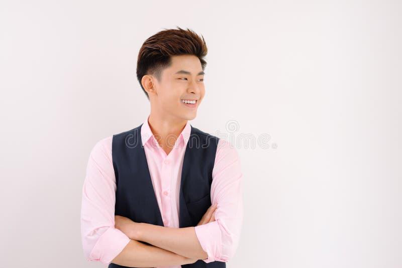 Support beau et sourire asiatiques d'homme posant sur le fond gris photo libre de droits