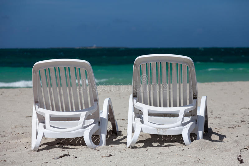 Support blanc de deux chaises de plage sur le bord de mer photographie stock