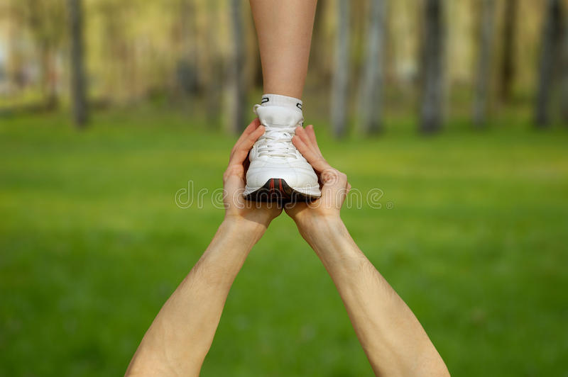 Support Concept. Two strong male hands holding one female foot. Teamwork, support, help, gymnastics, competition concepts royalty free stock photography
