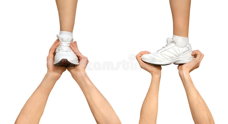 Support Concept. Two strong male hands holding one female foot. Teamwork, support, help, gymnastics, competition concepts. Isolated on white background royalty free stock images