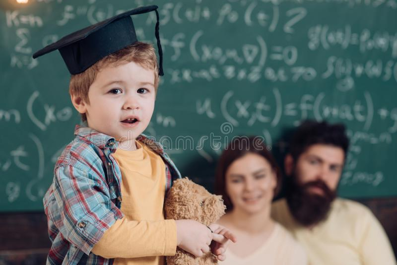Support concept. Kid holds teddy bear and performing. Parents listening their son, chalkboard on background. Smart child royalty free stock image