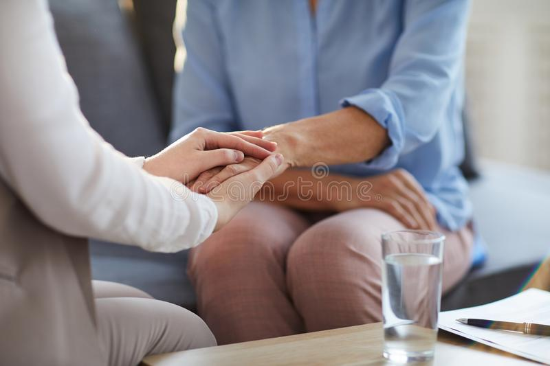 Support of counselor. Young professional counselor holding hand of mature women while giving her advice and supporting her stock photography