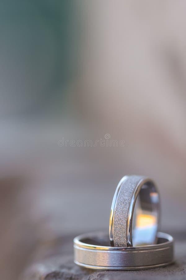 Support d'anneaux de mariage d'or blanc sur la roche noire Fond brouillé image libre de droits