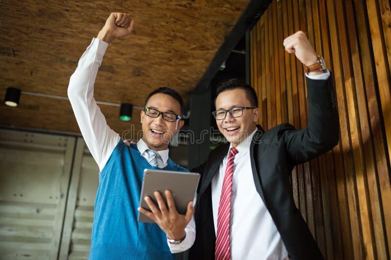 Support d'homme d'affaires de deux Asiatiques et regarder le comprimé, ils gais et célébrés le sien réussi dans la mission photo libre de droits