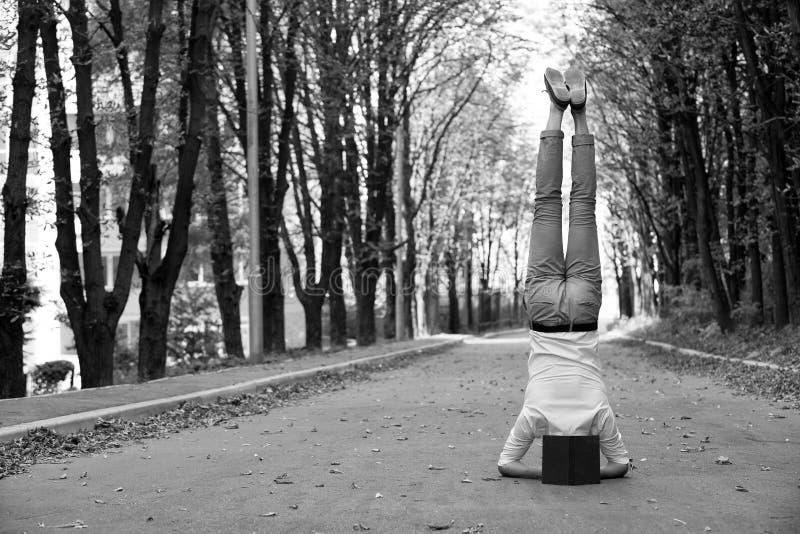 Support d'homme sur la tête sur la route de parc Étudiant avec le livre à l'envers en automne extérieur Fonctionnez l'équilibre d photos libres de droits