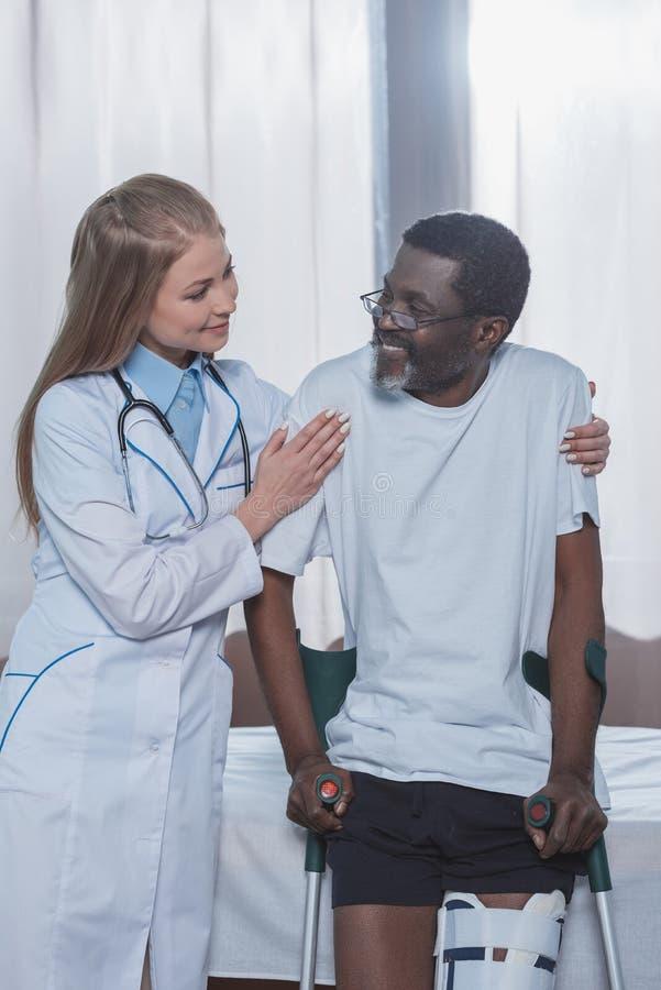 Support de aide de jeune docteur féminin jusqu'au patient masculin d'afro-américain avec l'accolade de jambe images libres de droits