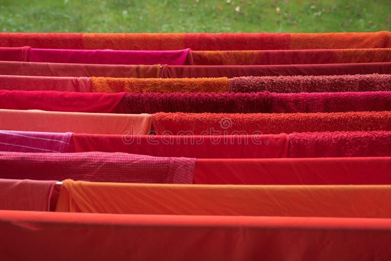 Support de blanchisserie dans le jardin avec sécher les vêtements et les serviettes rouges photos libres de droits