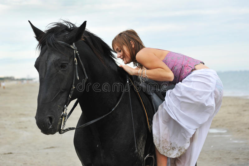 Support de femme un cheval sur la plage photo stock