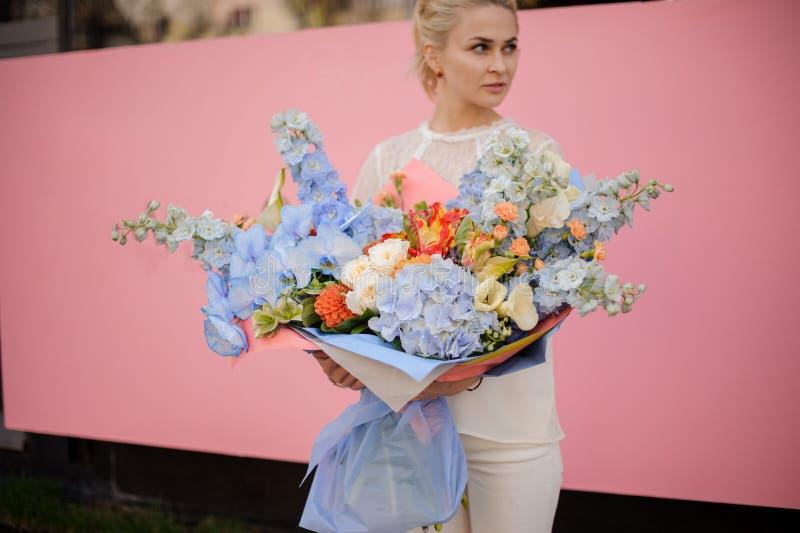 Support de fille avec le grand bouquet des fleurs bleues photos stock
