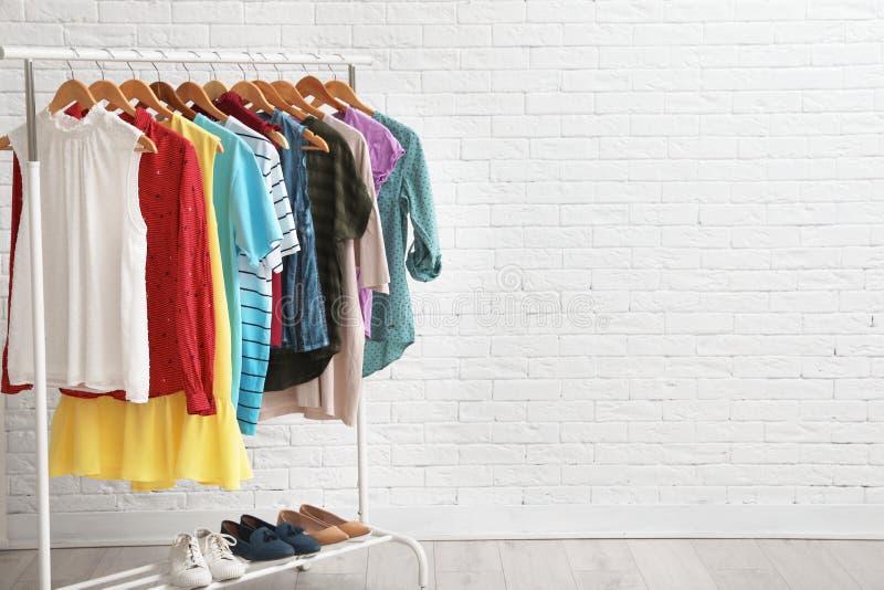 Support de garde-robe avec les vêtements et les chaussures élégants près du mur de briques à l'intérieur photographie stock
