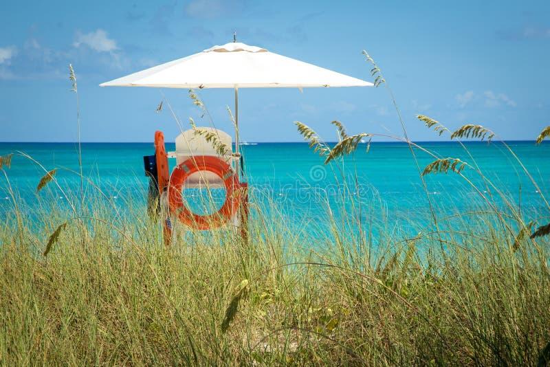 Support de maître nageur avec le parapluie blanc et l'orange bouy sur la plage en Îles Turques et Caïques image libre de droits