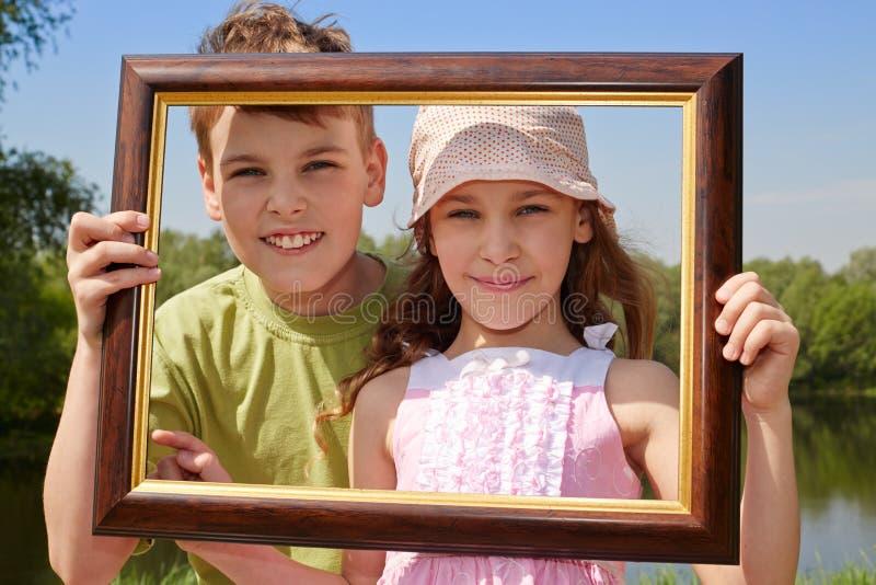 Support de sourire de fille et de garçon dehors, tenant le cadre de tableau image stock