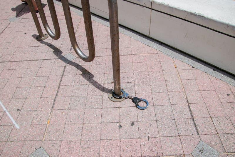 Support de vélo sur un trottoir de brique avec un type serrure de menotte de bicyclette attachée à un des tuyaux images libres de droits