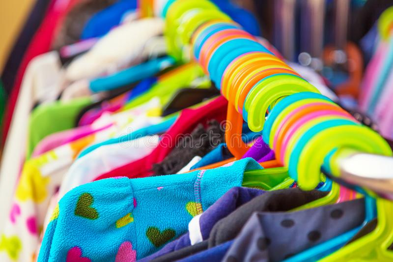 Support du bébé et les vestes et les vêtements d'enfants montrés au marché extérieur de cintre à vendre photos libres de droits