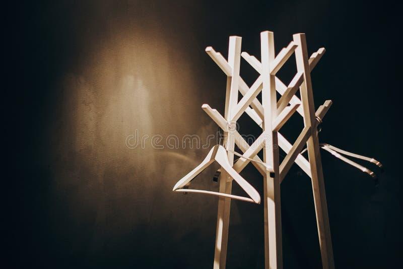 Support en bois de cintre élégant dans la lumière dans la chambre d'hôtel sombre Cintres en bois blancs modernes Armoire vide Pré image stock