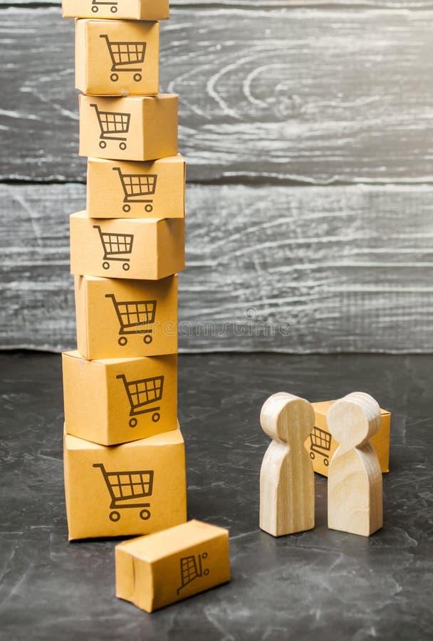 Support en bois de deux personnes près d'une tour des boîtes acheteur et vendeur, fabricant et détaillant Examen des termes du co photos libres de droits